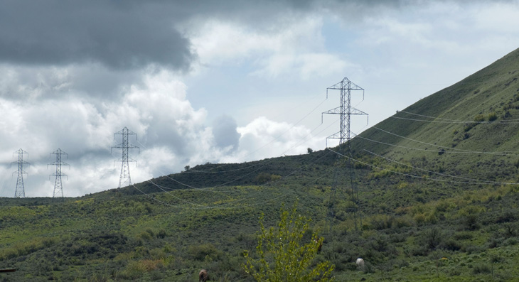 Tall structures holding up power lines along green hills.